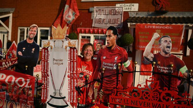 Penggemar Liverpool Emily Farley duduk di luar rumahnya, dihiasi dengan spanduk Liverpool dan cut out saat ia menunggu hasil pertandingan antara Manchester City dan Chelsea, di Liverpool, Inggris (25/6/2020). (AFP Photo/Oli Scarff)