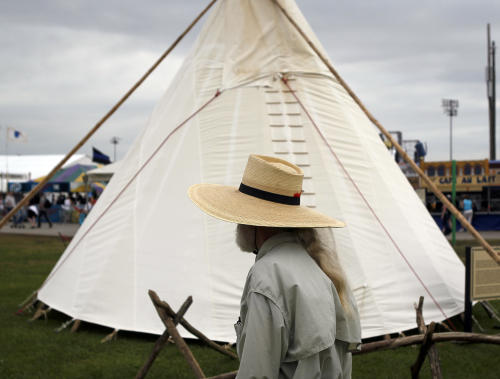 In this Friday, April 26, 2013 photo, a festival-goer passes by a teepee on display at the Cultural Exchange Pavilion during the New Orleans Jazz and Heritage Festival, in New Orleans. Louisiana Native Americans have long been represented at Jazz Fest, but this is the first year the focus on the culture has been expanded to include tribal nations from elsewhere in the United States, as well as Canada and Latin America. (AP Photo/Doug Parker)