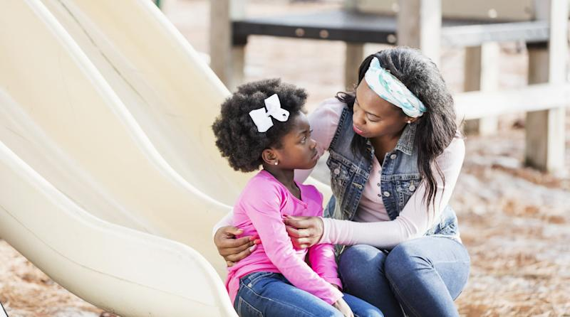 A young African-American woman helping her 5 year old daughter who is sitting on a slide on a playground with a sad expression on her face.