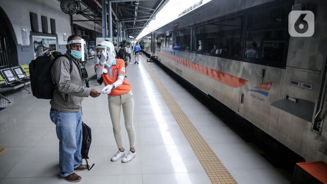 Petugas melayani calon penumpang di Stasiun Pasar Senen, Jakarta, Jumat (10/7/2020). PT KAI telah mengoperasikan lima perjalanan kereta jarak jauh untuk tujuan Bandung, Cirebon, dan Surabaya mulai Jumat 10 Juli 2020. (Liputan6.com/Faizal Fanani)