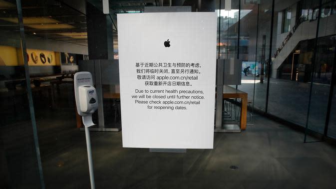 Apple Store memajang pemeritahuan penutupan tokonya di Beijing, China, Senin (10/2/2020). Apple Store di China dibuka kembali dalam waktu terbatas, pukul 11.00 hingga 18.00. (AP Photo/Andy Wong)