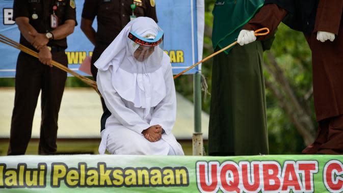 Salah seorang pasangan terpidana kasus zina (tengah) menjalani hukuman cambuk di Masjid Al Munawarah, Kota Jantho, Aceh Besar, Jumat (4/9/2020). Pasangan terpidana yang terbukti melanggar Syariat Islam dalam kasus zina itu masing masing menjalani sebanyak 100 cambuk. (CHAIDEER MAHYUDDIN/AFP)