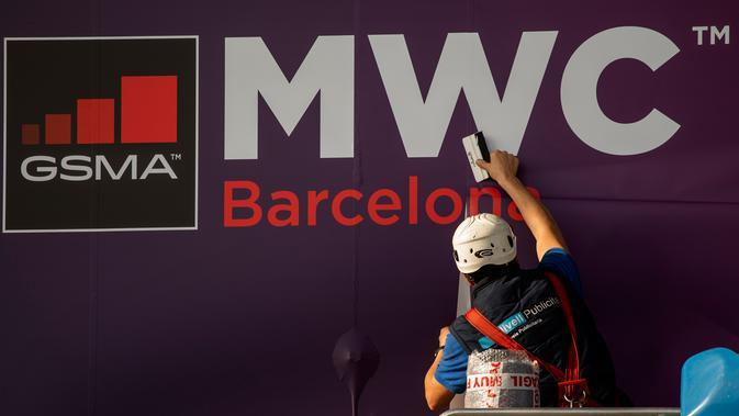 Pekerja memperbaiki poster yang mengumumkan Mobile World Congress (MWC) 2020 di lokasi pameran di Barcelona, Spanyol, Selasa (11/2/2020). Total kerugian akibat dibatalkannya MWC 2020 diperkirakan mencapai Rp 7,3 triliun). (AP Photo/Emilio Morenatti)