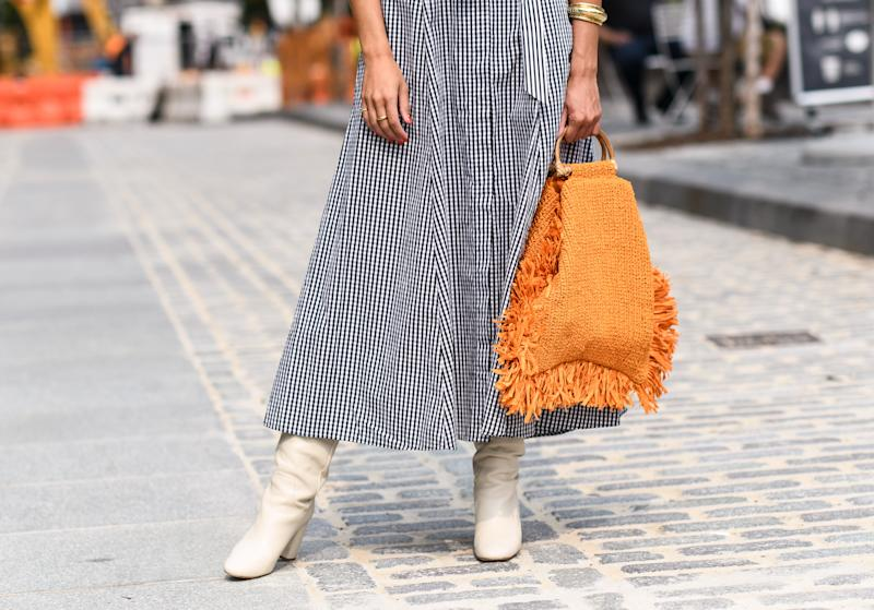 A guest is seen wearing checkered black and white dress with an orange bag and white boots outside the Alice and Olivia show during New York Fashion Week S/S21 on September 16, 2020 in New York City. (Photo by Daniel Zuchnik/Getty Images)