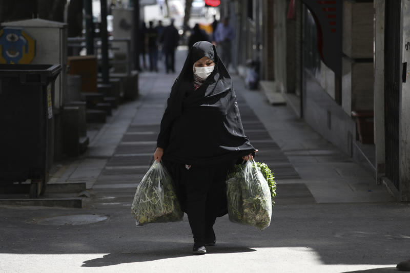 A woman wearing a face mask to protect against the new coronavirus carries her shopping in northern Tehran, Iran, Saturday, April 4, 2020. In the first working day after Iranian New Year holidays authorities have allowed some government offices and businesses to re-open with limited working hours, when schools, universities, and many businesses still are ordered to be closed aimed to prevent the spread of the virus.  (AP Photo/Vahid Salemi)
