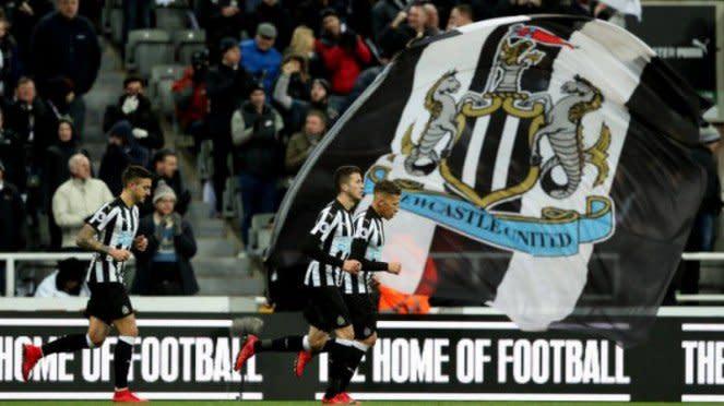 Para pemain Newcastle United berlari di depan bendera