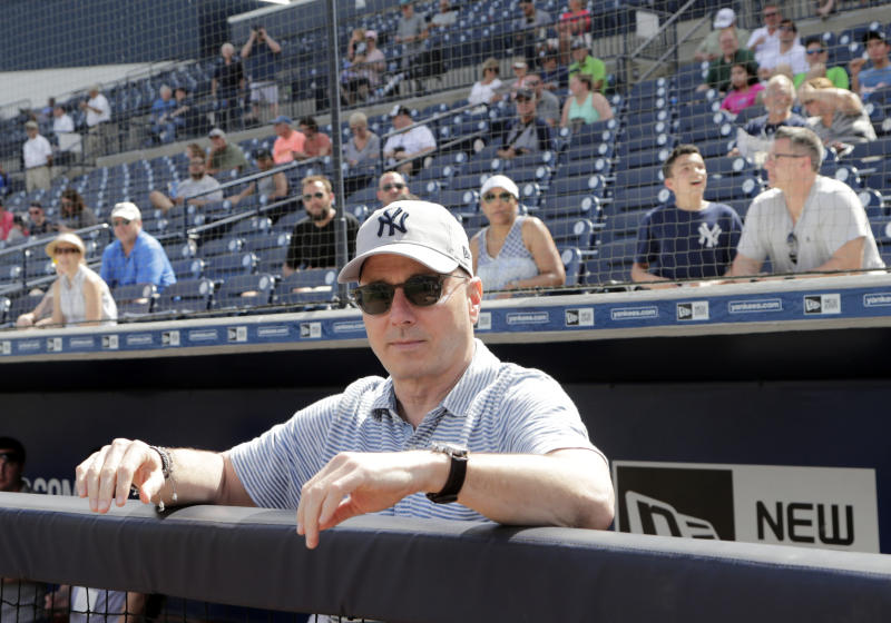 New York Yankees General Manager Brian Cashman looks out from the dugout at baseball spring training camp, Wednesday, Feb. 21, 2018, in Tampa, Fla. (AP Photo/Lynne Sladky)