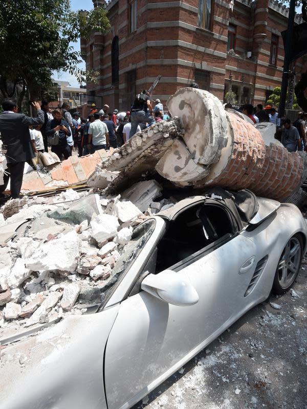 Sebuah mobil yang hancur tertimpa bangunan setelah gempa mengguncang Kota Meksiko (19/9). Gempa terjadi tepat 32 tahun sejak gempa dahsyat menewaskan ribuan orang di Mexico City pada 1985. (AFP Photo/Alfredo Estrella)