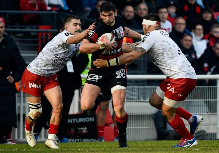 Toulon's Anthony Meric and Raphael Lakafia close in on Xavier Mignot, one of the Lyon try scorers