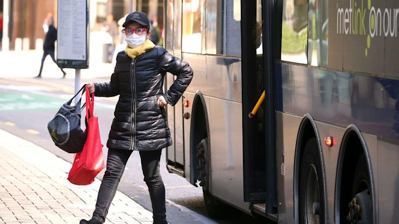 A woman wearing a face mask disembarks a public bus after a move to COVID-19 Alert Level 1 on September 22