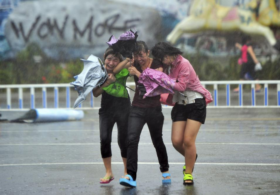 People cross a street against strong wind and heavy rainfall under the influence of Typhoon Haiyan, in Sanya