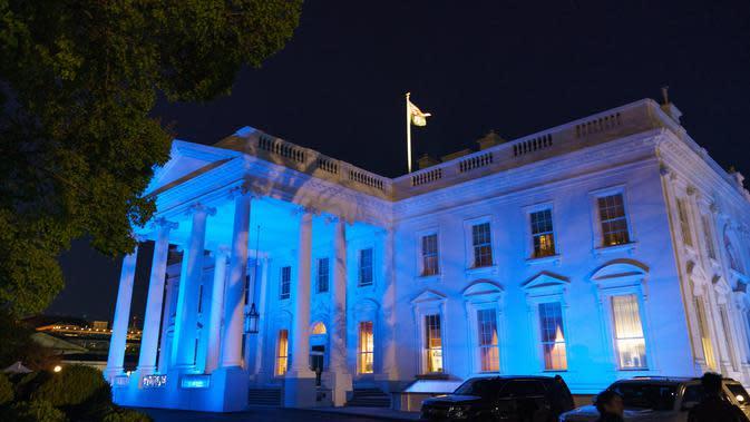 Gedung Putih menyala dengan warna biru untuk menandai World Autism Awareness Day atau Hari Peduli Autisme Sedunia di Washington, Kamis (2/4/2020). Hari Peduli Autisme Sedunia jatuh setiap 2 April semenjak ditetapkan melalui sebuah resolusi PBB di tahun 2007. (MANDEL NGAN / AFP)