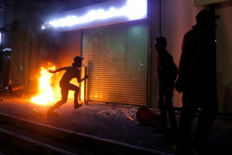 A protester kicks the entrance of a bank in Sidon