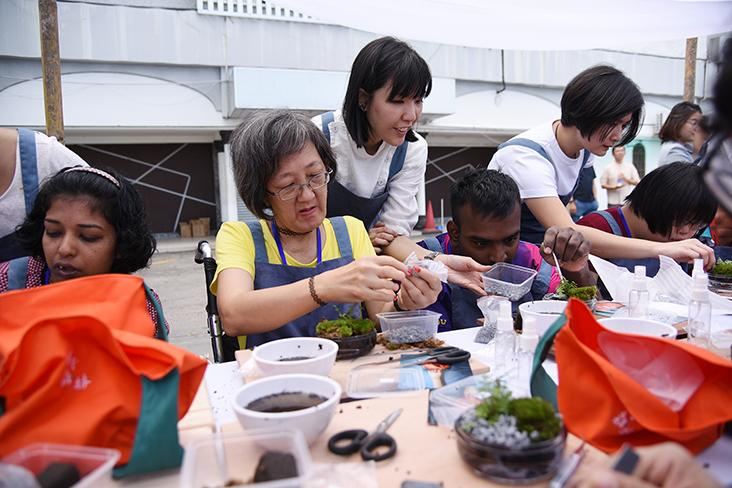 Ivy Gan (second from left) making her own miniature forest in a bottle at the workshop