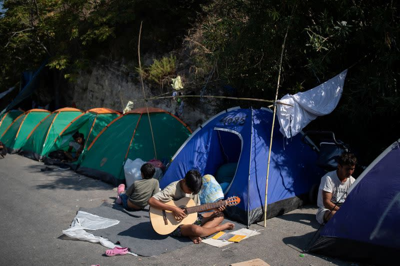 Greece struggles to bring migrants into temporary camp after fire