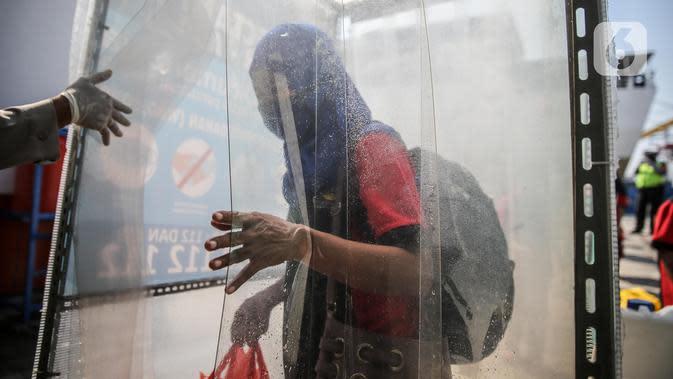 Seorang TKI Ilegal yang dipulangkan dari Malaysia keluar dari bilik disinfektan setibanya di Pelabuhan Tanjung Priok, Jakarta, Jumat (12/6/2020). Sebanyak 436 TKI Ilegal tersebut nantinya akan dipulangkan ke daerah asalnya di 22 provinsi. (Liputan6.com/Faizal Fanani)