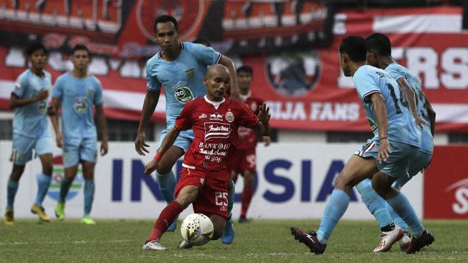 Gelandang Persija Jakarta, Riko Simanjuntak, berusaha melewati pemain Persela Lamongan pada laga Shopee Liga 1 di Stadion Wibawa Mukti, Bekasi, Jumat (15/11). Persija menang 4-3 atas Persela. (Bola.com/Yoppy Renato)