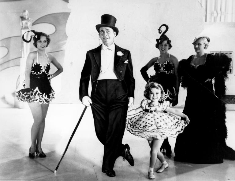 """FILE - This undated file photo shows six-year-old Shirley Temple as she appears in her first featured role in the 1934 musical """"Stand Up and Cheer"""" with James Dunn. (AP Photo, File)"""