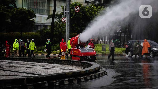 Petugas pemadam kebakaran menyemprotkan cairan disinfektan menggunakan robot LUF 60 di kawasan Bundaran HI, Jakarta, Minggu (22/3/2020). Penyemprotan untuk mencegah penyebaran virus corona COVID-19 ini dilakukan di lima wilayah Ibu Kota. (Liputan6.com/Faizal Fanani)