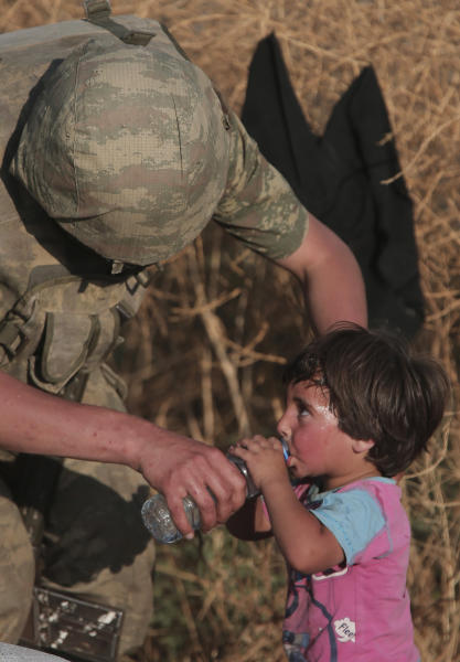 File - In this June 14, 2015, file photo a Turkish soldier offers water to a Syrian refugee child after crossing into Turkey from Syria, in Akcakale, Sanliurfa province, southeastern Turkey. As Turkish forces invaded northern Syria in early October 2019, supporters of the offensive launched an online misinformation campaign. Dozens of misleading images claiming to show Turkey's soldiers cuddling babies, feeding hungry toddlers and carrying elderly women spread across Twitter and Instagram where they were liked, retweeted and viewed thousands of times. They included this photo, which was, in fact, shot by an Associated Press photographer in 2015. (AP Photo/Lefteris Pitarakis, File)