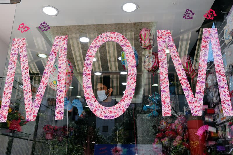 A worker is seen through a flower shop window as flower shops are open exceptionally for Mother's Day, in Beirut