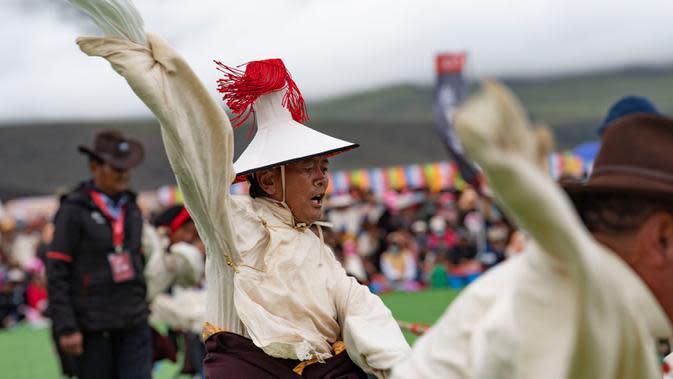 Seorang penggembala menyemangati rekan timnya dalam kompetisi tarik tambang di Wilayah Damxung, Daerah Otonom Tibet, China, 10 Agustus 2020. Dengan pakaian tradisional, para penggembala dari sejumlah desa di Wilayah Damxung berpartisipasi dalam permainan tradisional itu. (Xinhua/Purbu Zhaxi)