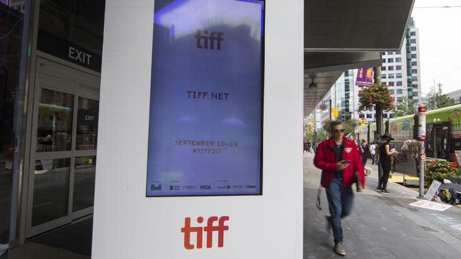 Pria berjalan melewati layar yang menampilkan informasi tentang ajang Toronto International Film Festival (TIFF) 2020 di Toronto, Kanada, 10 September 2020. TIFF 2020 akan berlangsung 10 hari mulai 10 September 2020 dengan lokasi drive-in dan pemutaran film secara daring (online). (Xinhua/Zou Zheng)