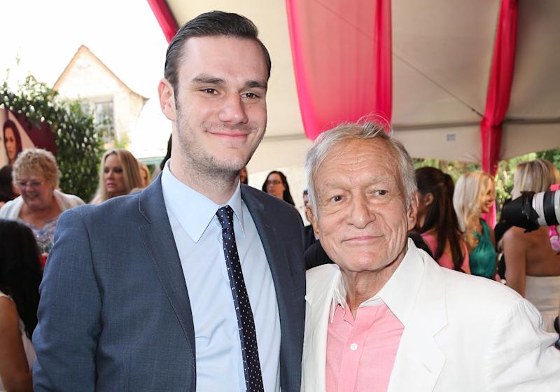 Playboy Founder Hugh Hefner (R) and and his son Cooper Hefner (L) attend the 2013 Playmate Of The Year announcement at The Playboy Mansion on May 9, 2013 in Beverly Hills, California.