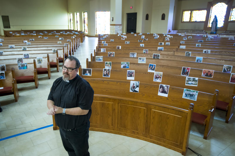 The Rev. Sean Horrigan, parish priest, stands in the sanctuary at Christ the Redeemer Catholic Church in front of photos of parishioners that are taped to the pews, which are part of virtual masses at the church, on Friday, April 10, 2020, in Houston. The coronavirus pandemic has shut down most religious services throughout the country and many churches are offering services through social media and video conferencing. (Brett Coomer/Houston Chronicle via AP)