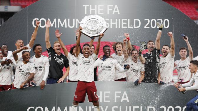 Striker Arsenal, Pierre-Emerick Aubameyang, mengangkat trofi juara Community Shield usai menaklukkan Liverpool di Stadion Wembley, Sabtu (29/8/2020). Arsenal menang adu penalti dengan skor 5-4. (Andrew Couldridge/Pool via AP)