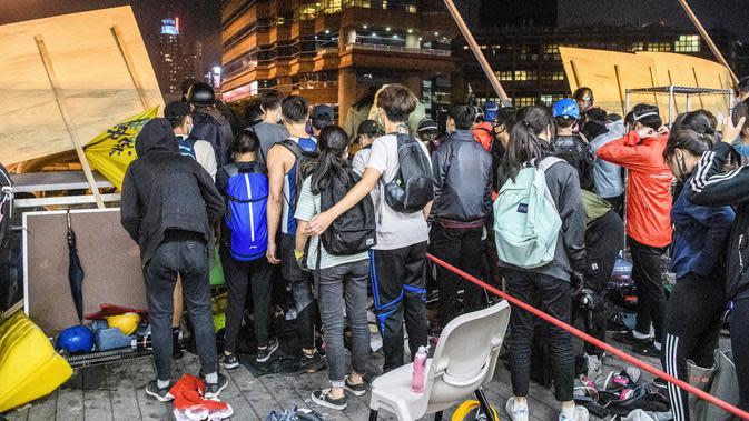 Demonstran antre menuruni jembatan menggunakan tali untuk melarikan diri dari Universitas Politeknik Hong Kong di Distrik Hung Hom, Hong Kong, Senin (18/11/2019). Lusinan demonstran melarikan diri dari Universitas Politeknik Hong Kong yang dikepung polisi selama berhari-hari. (ANTHONY WALLACE/AFP)