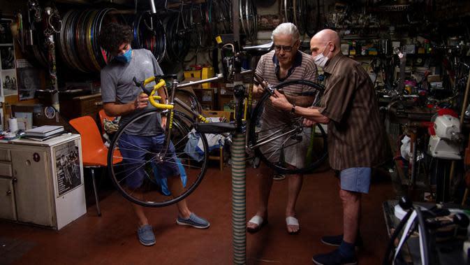 Raffaello Bianco, mekanik dan pecinta sepeda bekerja di bengkel mekaniknya di ruang bawah tanah apartemennya di Turin, Italia, 7 Juli 2020. Di antara banyak pesepeda amatir yang memintanya untuk memperbaiki sepeda mereka, ada pengendara profesional seperti Fabio Fellini. (MARCO BERTORELLO/AFP)