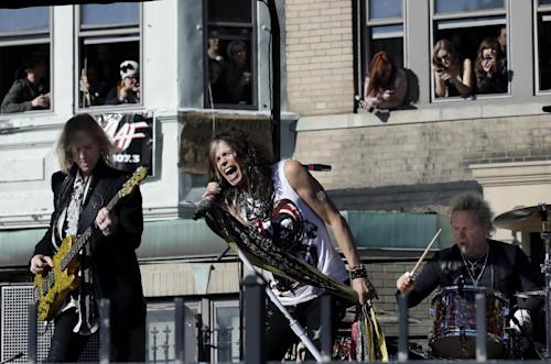 Aerosmith members, from left, Tom Hamilton, Steven Tyler and Joey Kramer perform a free concert Monday, Nov. 5, 2012 in Boston's Allston neighborhood as fans watch from the apartment building which was their home in the early 1970's. (AP Photo/Elise Amendola)