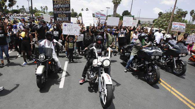 Pengunjuk rasa berbaris saat memprotes kematian George Floyd di Compton, California, Amerika Serikat, Minggu (7/6/2020). Gelombang protes atas kematian George Floyd terus mengguncang Amerika Serikat. (AP Photo/Marcio Jose Sanchez)