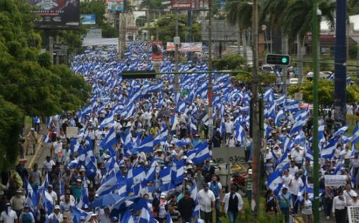 A sea of blue and white Nicaraguan flags fills an avenue in Managua during a march in the capital city