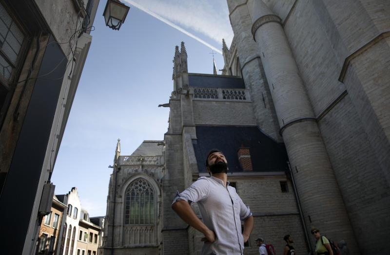 In this photo taken on Wednesday, June 24, 2020, history teacher Andries Devogel looks up toward a falcon nest on the Saint Martin Basilica in Halle, Belgium. Much responsibility will be put on young history teachers like Andries Devogel in the coming decade, with the expectation to stress the impact of colonialism on current-day society. (AP Photo/Virginia Mayo)