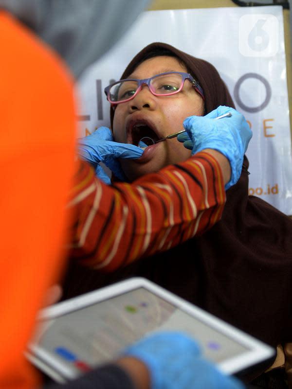 Seorang perempuan menjalani pemeriksaan kesehatan gigi saat berlangsung layanan gratis di Stasiun MRT Bundaran HI, Jakarta, Rabu (4/12/2019). Pemeriksaan tersebut untuk penyandang disabilitas yang menjadi penumpang MRT serta edukasi cara merawat gigi yang benar. (merdeka.com/Imam Buhori)