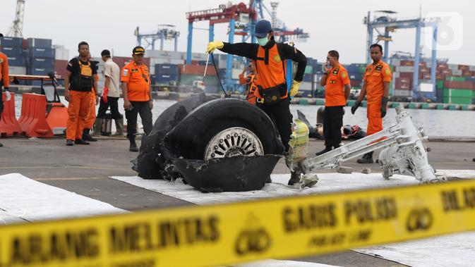 File foto pada 5 November 2018 memperlihatkan petugas menyemprot cairan pada bagian roda pesawat Lion Air PK-LQP JT 610 di Pelabuhan JICT 2, Jakarta. Bagian tersebut dipindah untuk dilakukan identifikasi dan pengecekan lebih lanjut oleh KNKT. (Liputan6.com/Helmi Fithriansyah)