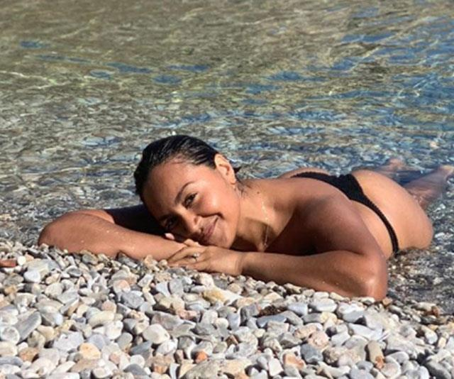 Jessica Mauboy lying on a beach showing off engagement ring