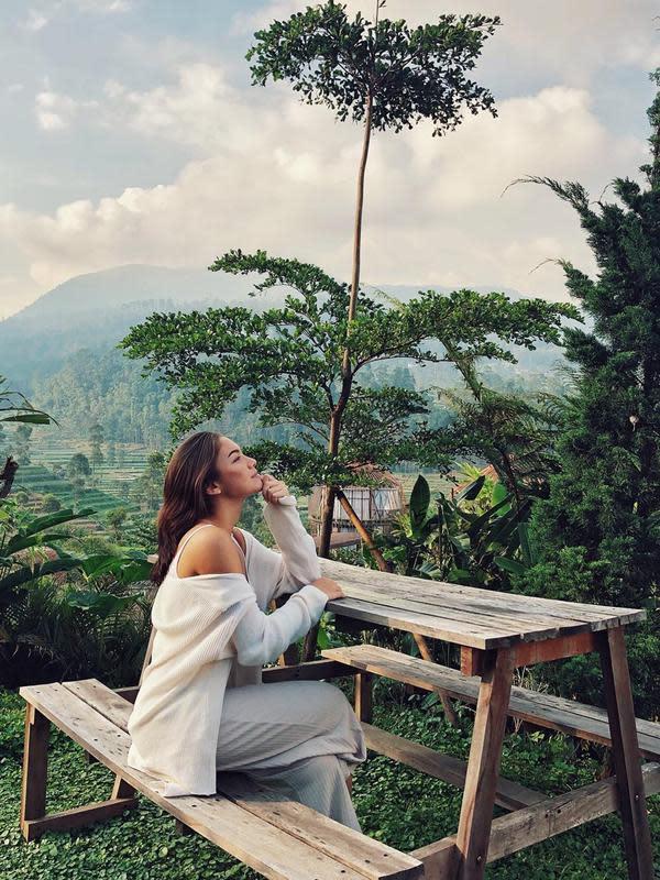 Tak sedikit netizen yang turut memberikan komentar pujian atas penampilan sederhana dari Angela Gilsha. Pada foto ini pun Angela terlihat sangat menikmati pemandangan hijau dan pegunungan yang ada. (Liputan6.com/IG/@angelagilsha)