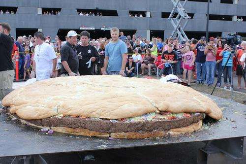 In this Sunday, Sept. 2, 2012 photo provided by by Black Bear Casino Resort, people examine a bacon cheeseburger measuring 10 feet in diameter and weighing more than a ton at Black Bear Casino Resort near Carlton, Minn. The behemoth burger, served up Sunday at the Black Bear Casino Resort tipped the scales at 2,014 pounds. (AP Photo/