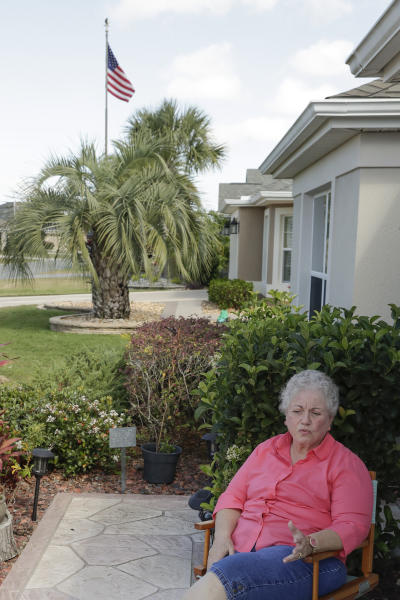 In this Thursday, March 19, 2020 photo, Shirley Schantz, at her home, discusses current issues living in a retirement community in The Villages, Fla. Due to the coronavirus all regularly-scheduled indoor activities were canceled through the end of the month for residents living in what is perhaps the largest concentration of seniors in the U.S. (AP Photo/John Raoux)