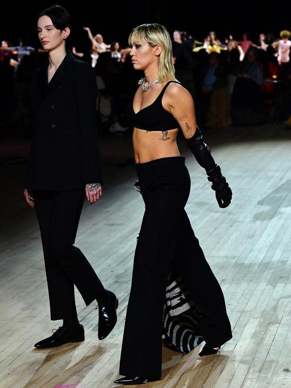 Miley Cyrus (kanan) berjalan di catwalk untuk show Marc Jacobs Fall 2020 selama New York Fashion Week di New York City, Rabu (12/2/2020). Miley Cyrus bergabung dengan sejumlah model di runway termasuk, Gigi Hadid dan adiknya, Bella Hadid serta Kaia Gerber. (Slaven Vlasic/Getty Images/AFP)