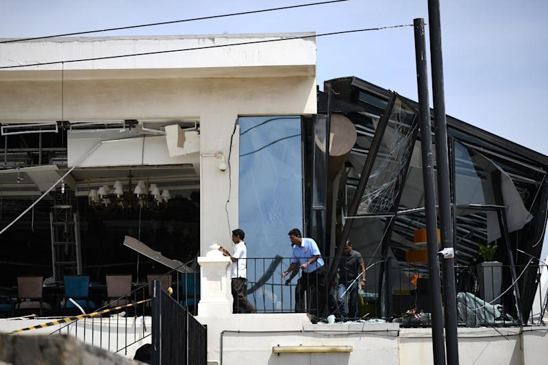 Three men inspect damage from the roof of a restaurant at the Kingsbury Hotel in Colombo. Source: Getty Images