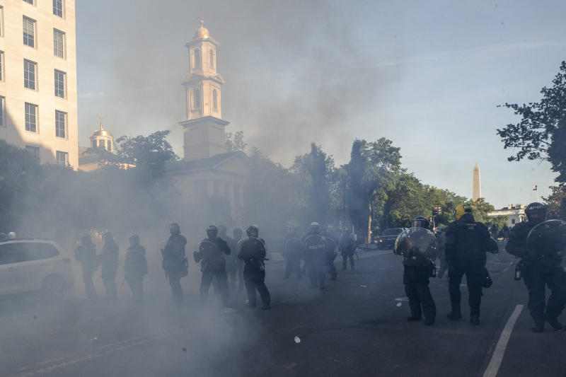 Tear gas floats in the air as a line of police move demonstrators away from St. John's Church across Lafayette Park from the White House, as they gather to protest the death of George Floyd, Monday, June 1, 2020, in Washington. Floyd died after being restrained by Minneapolis police officers. (AP Photo/Alex Brandon)