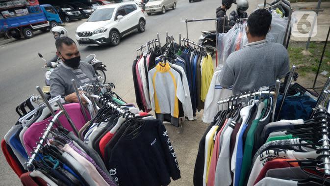 Ridwan (40) menata baju seken (baju bekas) impor di Pamulang, Tangerang Selatan, Banten, Senin (29/9/2020). Pada saat pandemi baju bekas impor masih diminati masyarakat karena murah harganya. (merdeka.com/Dwi Narwoko)
