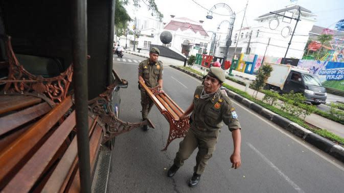 Antisipasi penyebaran COVID-19, Satpol PP Kota Bandung bekerja sama dengan Dinas Pekerjaan Umum dan Dinas Perumahan dan Kawasan Permukiman, Pertanahan dan Pertamanan Kota Bandung (DPKP3), mencabut sementara kursi yang berada di seputaran Taman Alun-alun Bandung. (sumber foto : Humas Pemda Bandung)