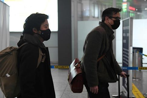 Wall Street Journal reporters Josh Chin (right) and Philip Wen walk through Beijing Capital Airport before their departure on February 24 after being expelled over a controversial headline in an op-ed that angered Beijing. Photo: AFP