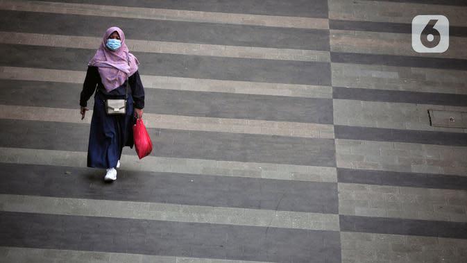 Pegawai pulang kerja menyeberang di Jalan Sudirman, Jakarta, Selasa (12/5/2020). Pemerintah memberi kelonggaran bergerak bagi warga berusia di bawah 45 tahun untuk mengurangi angka pemutusan hubungan kerja (PHK) akibat pandemi virus corona COVID-19. (Liputan6.com/Johan Tallo)