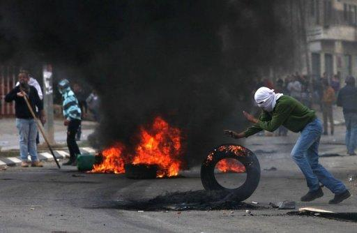 A Palestinian student from Birzeit University pushes a burning tire during clashes with Israeli soldiers for the second consecutive day as they protest against the ongoing Israeli offensive on the Gaza Strip in the West Bank town of Betunia on November 18, 2012